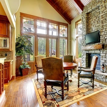 Luxury mountain home diining and living room with stone fireplace.